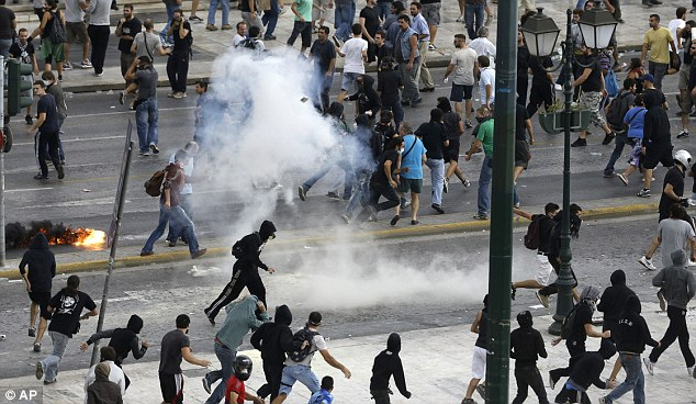 Storm cloud: Protesters turn and flee as police use tear gas