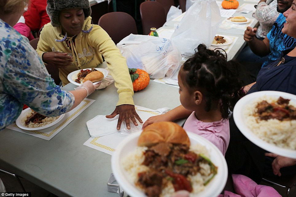 Families eat dinner at the Cathedral Kitchen soup kitchen which feeds hundreds of hungry mouths a day, six days a week