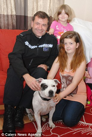 Family reunion: Katiecorr, six, and Kiracorr, 12, proudly pose with the Staffordshire bull terrier and Pc John Shaddick after the dog's safe return