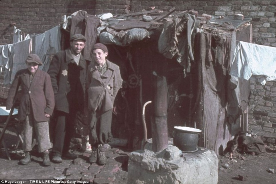 Ghetto boys: In their tattered rags the two boys smile for the camera, but the man in the centre, most probably their father, has a look of distrust etched across his face