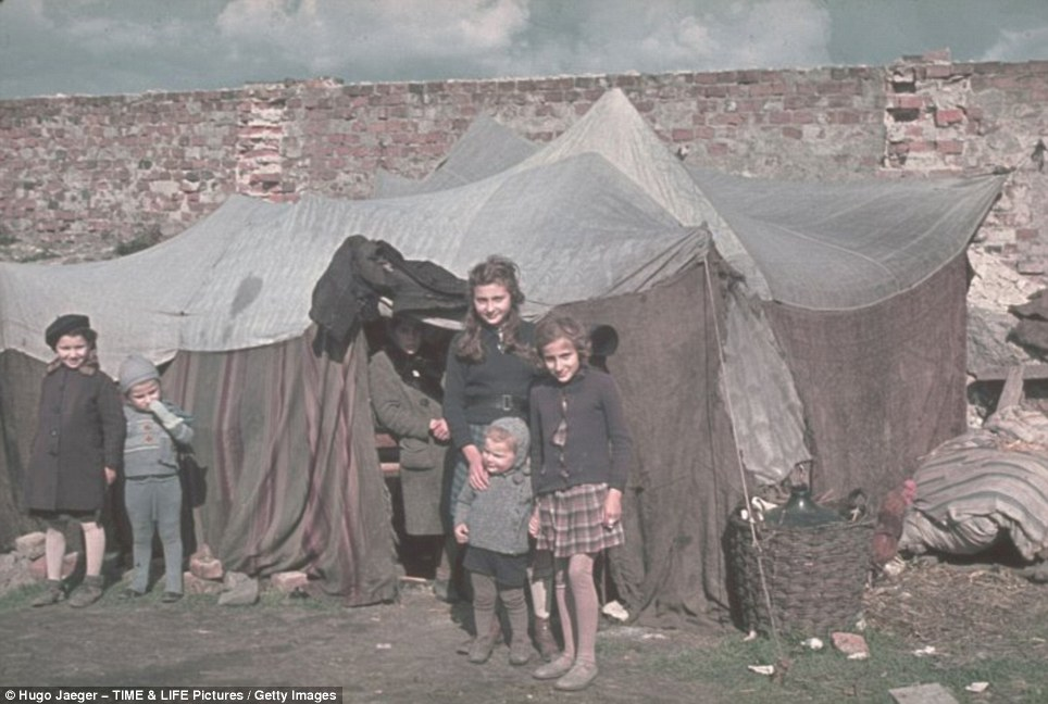 Innocent victims: These young Jewish girls couldn't possibly have imagined the horrors that lay ahead as they pose outside their tent in another haunting photograph taken by the ardent Nazi Hugo Jaeger