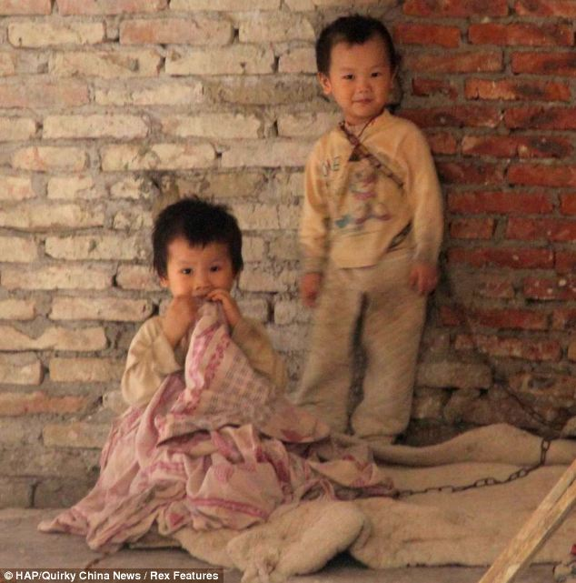 Tragic: The children are left chained up at a building site by their parents in Guangzhou, southern China - because they cannot afford the cost of childcare