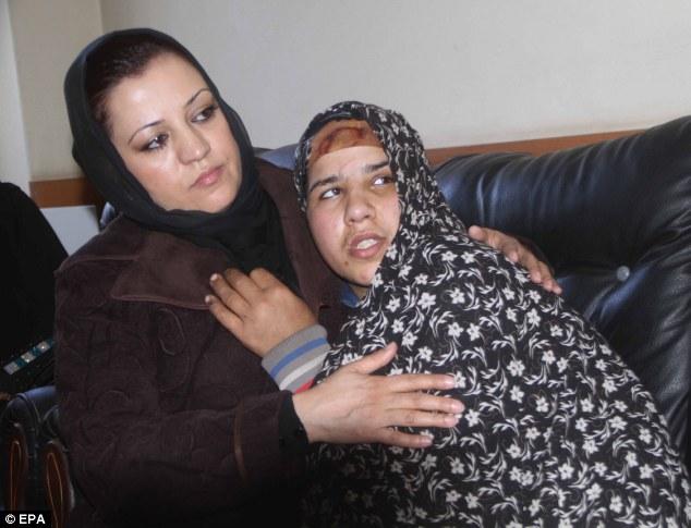 Dos caras: Maria Bashir, fiscal general de Herat reconfortante Arefa, una víctima de violencia doméstica, en Herat, Afganistán, el año pasado