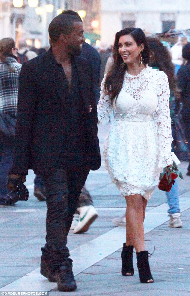 A rare smile: Kanye finally cracks a smile as he looks adoringly at Kim