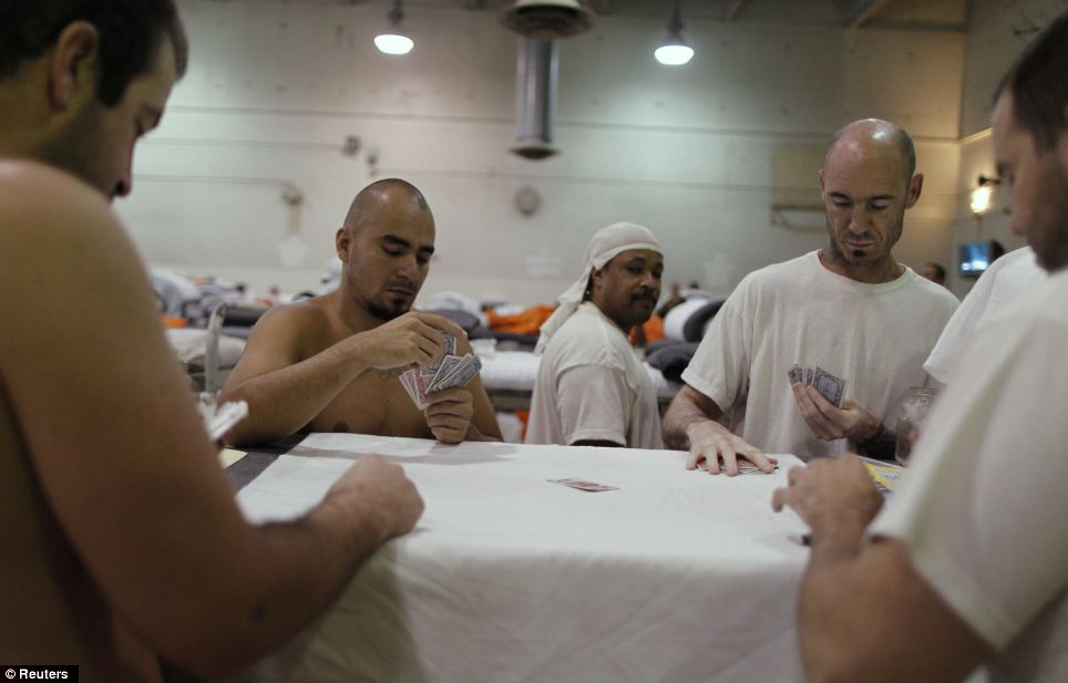 A makeshift living space for prisoners doubles up as a recreation area at this prison in Chino, California, with a group of inmates using the bed as a poker table