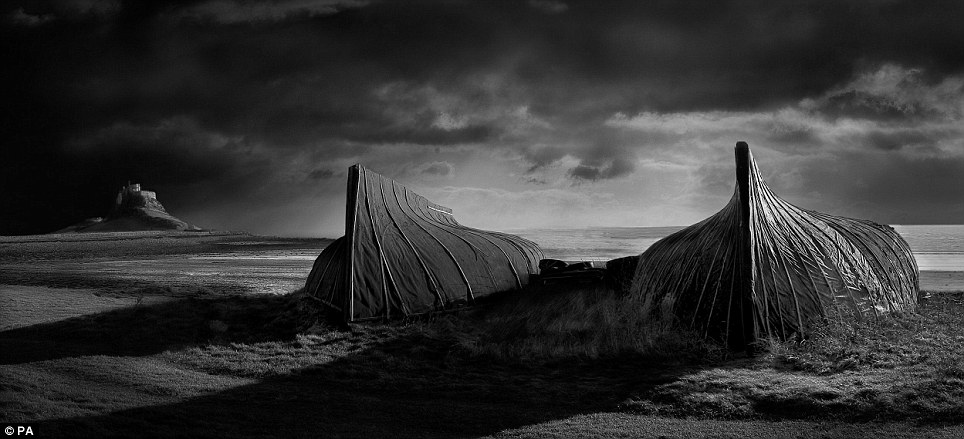 Striking: David Byrne's picture of upturned boats on the coast of Lindisfarne, Northumberland, England, was doctored to include clouds in the sky to make it look darker and gloomy
