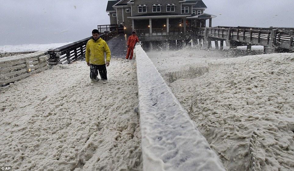 No es una espuma party: A vadea noticias valientes tripulantes a través de la espuma del mar sopla sobre Pier de Jeanette en Kill Devil Hills, Carolina del Norte como el viento y la lluvia del huracán movimiento de arena en la zona