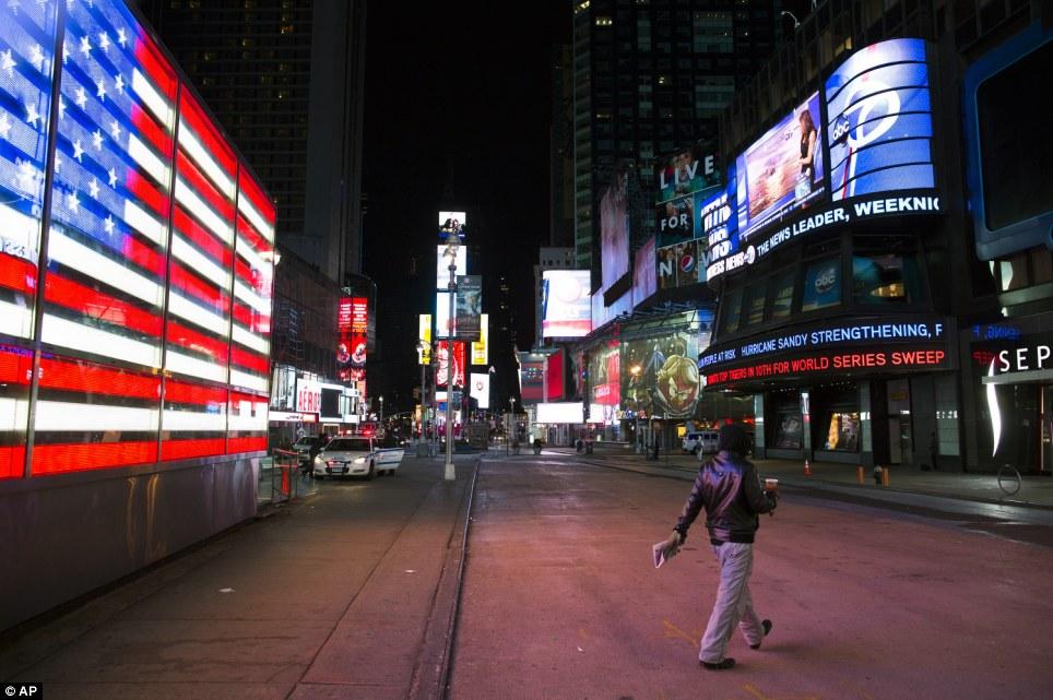 Vacío: Un peatón solitario camina a través de un Times Square vacíos el lunes, pocas horas antes de cuando Sandy se espera para atacar la ciudad