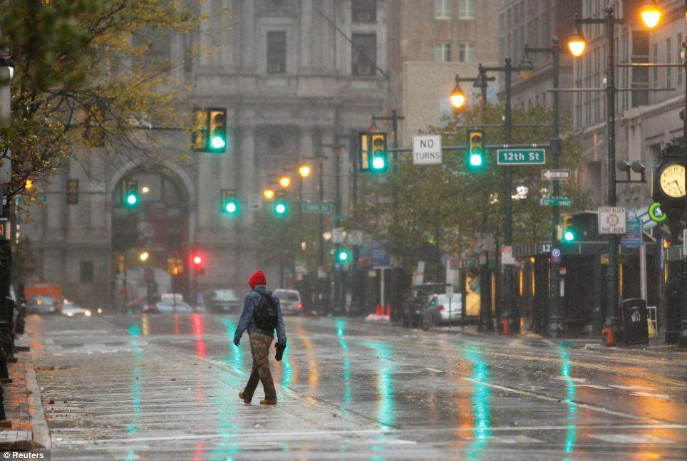 El enfoque: Un peatón cruza una calle de mercado libre con vientos y lluvias del huracán en Philadelphia, Pennsylvania