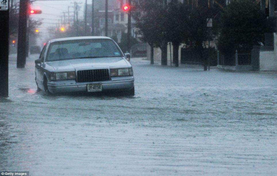 Recopilación de tormenta: Un coche se encuentra en una calle inundada cerca del océano delante del huracán de arena en Atlantic City, Nueva Jersey el lunes