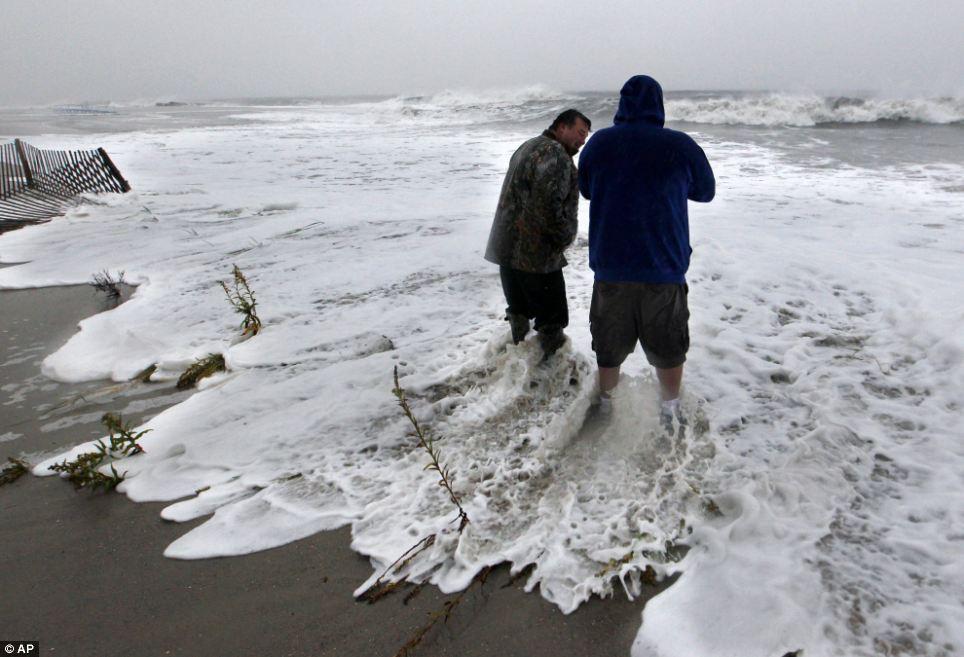 Frente a la tormenta: Andy Becica, izquierda, y Peter Wilson estar en fuerte oleaje a lo largo de la mañana del Océano Atlántico el lunes en Cape May, Nueva Jersey