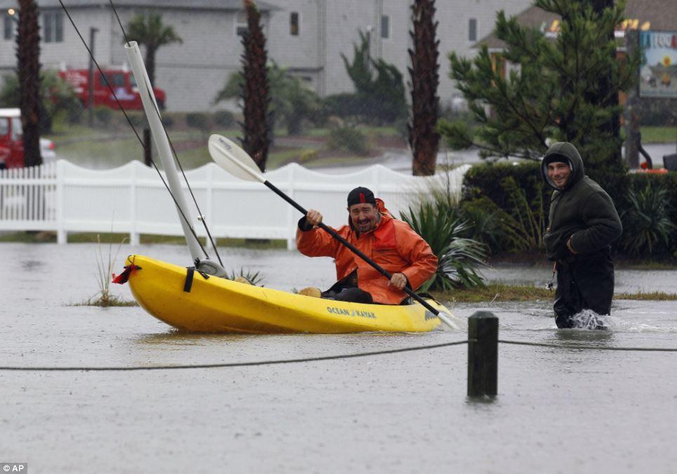 En su paso: Allen Boyer remos un kayak en aguas de la inundación causada por el huracán de arena como Bobby Carnutte vadea a través del agua a la derecha en Kitty Hawk, Carolina del Norte