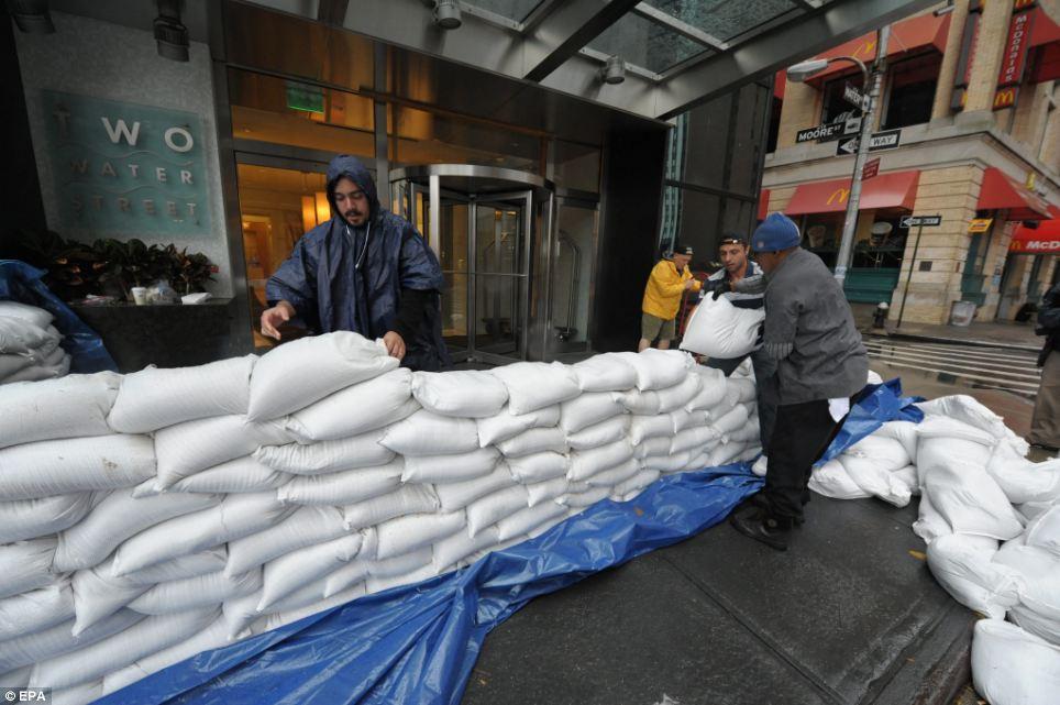 Preparación: Trabajadores poner sacos de arena en frente de un edificio en el distrito financiero ya que los efectos iniciales del huracán de arena se hacen sentir en Nueva York