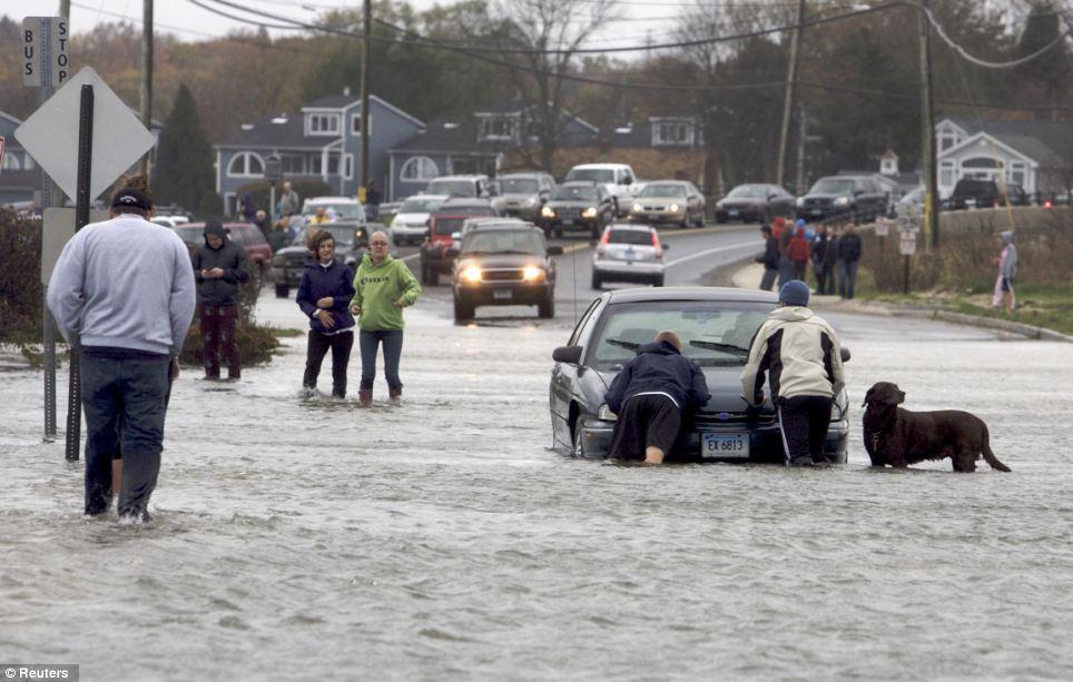 Trabajo en grupo: Los peatones acudir en ayuda de un motorista atrapado en una carretera inundada a lo largo de la zona marítimo terrestre de Milford, Connecticut
