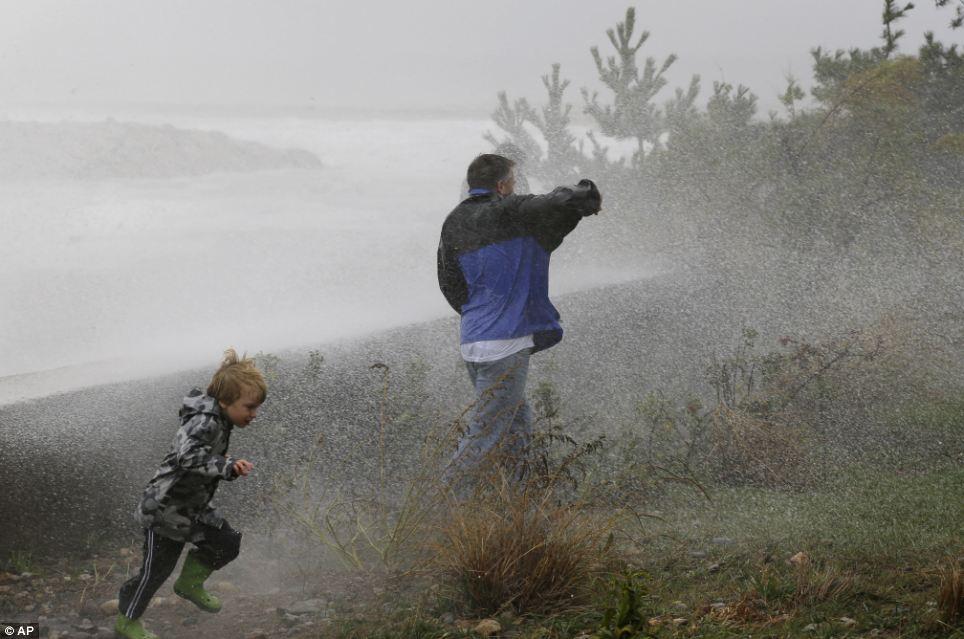 Corriendo por cubre: a apoyos de la familia en contra de Ocean Spray como choque de las olas contra un rompeolas en Scituate, Massachusetts el lunes