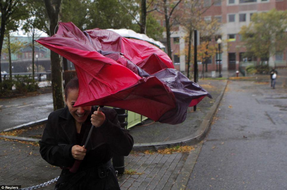 Ráfagas: Una mujer intenta ponerse a cubierto de la lluvia en Hoboken arena mientras se acerca a New Jersey con vientos máximos sostenidos de 90 mph