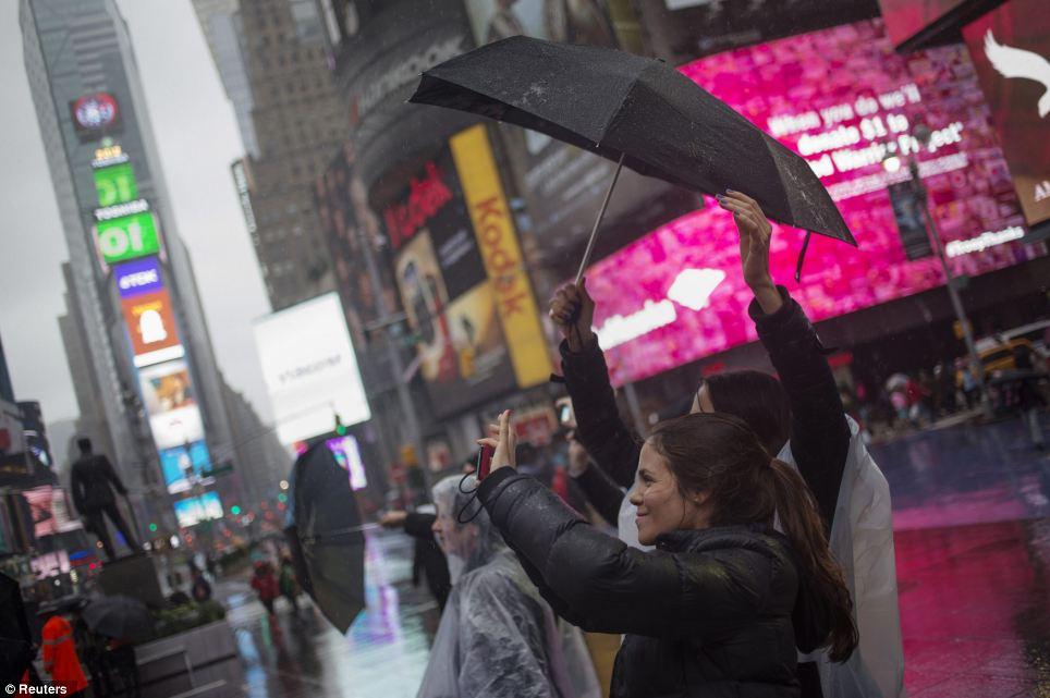 Mantener una actitud positiva: Los visitantes sostener paraguas mientras toma fotos durante la lluvia en Times Square en Nueva York