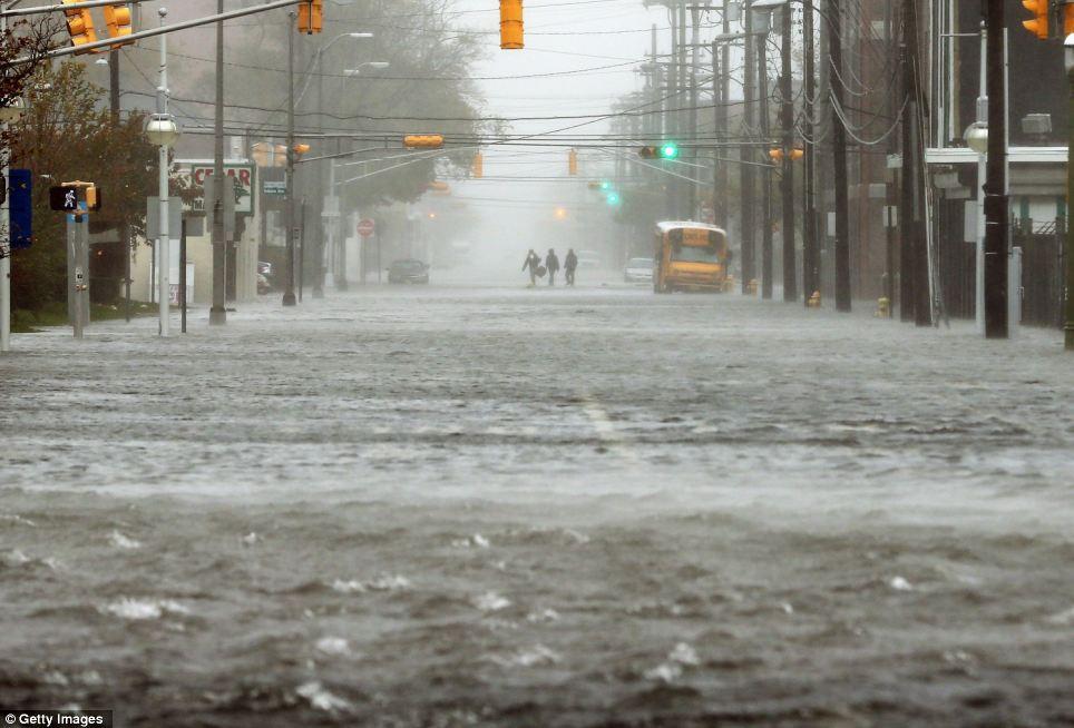 Inundado: La gente camina por una calle sumergida en Atlantic City, donde la tormenta tocó tierra el lunes más tarde