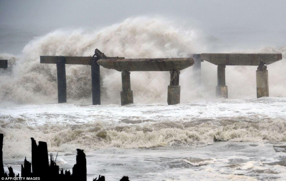 Vicious: choque de las olas contra un muelle dañado previamente antes de tocar tierra el huracán de arena el lunes antes de las inundaciones comunidades