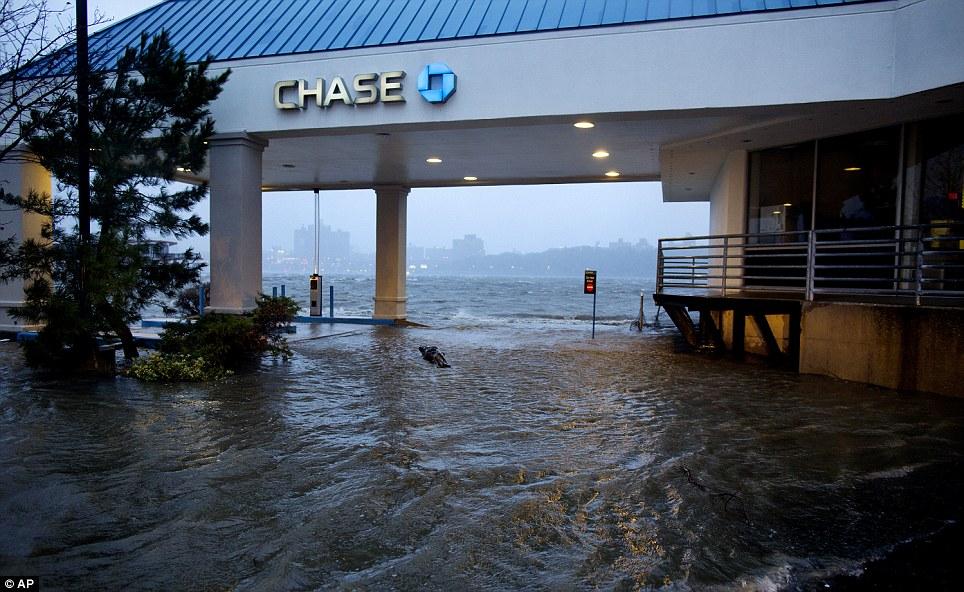 Amenaza: El aumento de agua desde el río Hudson alcanza un banco drive-through en Edgewater, Nueva Jersey