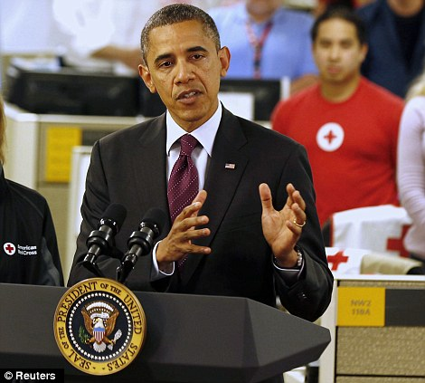 U.S. President Barack Obama (R) talks about damage done by Hurricane Sandy and rescue efforts while at the National Red Cross Headquarters in Washington