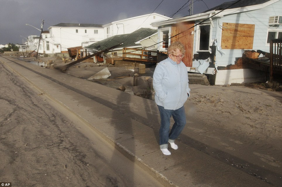 Distraught: A woman stares at the ground as she walks past damaged homes after the fire at Breezy Point in the Queens borough of New York