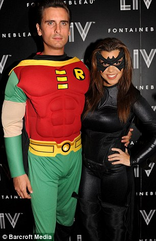Say cheese: Kourtney and Scott posed on the red carpet while, right, Kim and pal Jonathan Cheban, dressed as The Riddler