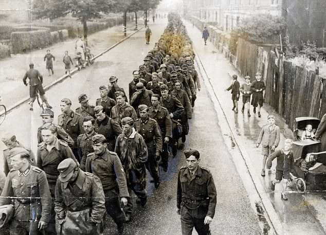 Prisoners: German soldiers are marched through an English village to a PoW camp in June 1944