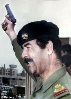 Former Iraqi President Saddam Hussein holds up a gun in 1991