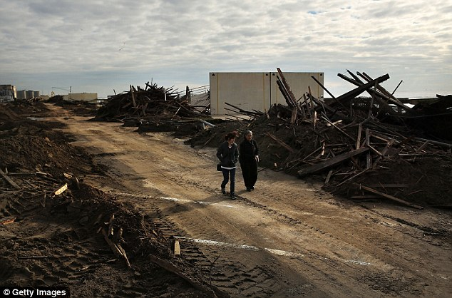 Wild west: People walk through the heavily damaged Rockaway neighborhood in Queens where a large section of the iconic boardwalk was washed away