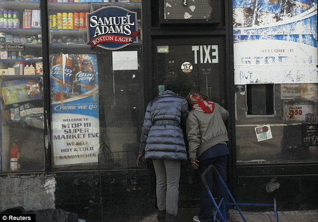 The hunger games: Two women look into the window of a flooded deli while searching for food in Coney Island, four days after Sandy