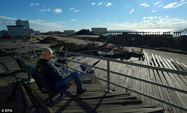 Damages: Jeff Kulikowski sits on a bench on the boardwalk that was pushed off of its pilings by storm surge in the Rockaways