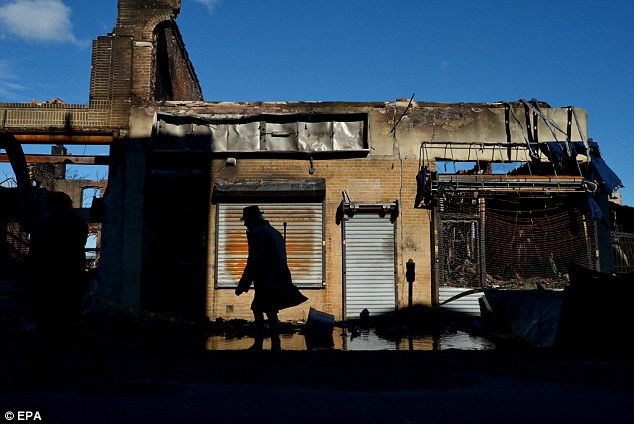 Ruins: A silhouetted man walks past a strip of destroyed buildings in Rockaways