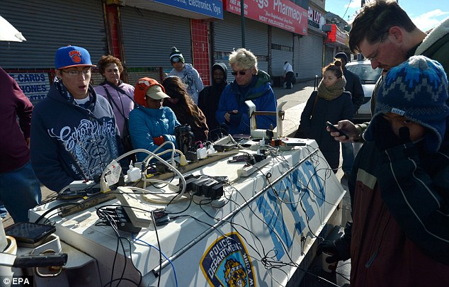 Keeping in touch: People charge cell phones at a police generator in Rockaways