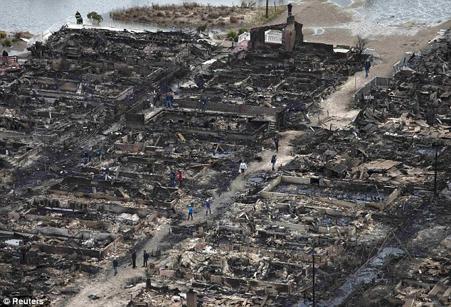 Residents walk past burned houses in Breezy Point, a neighborhood located in the New York City borough of Queens, after it was devastated by Hurricane Sandy