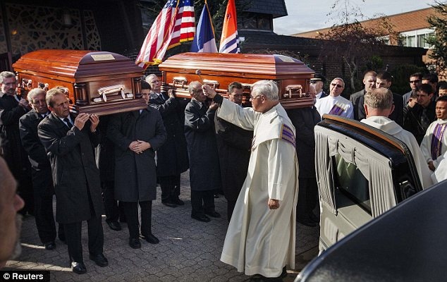Blessing: A priest douses holy water on the caskets following the funeral service