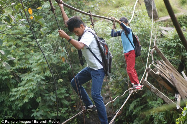 Children use wires to cross the river to get to school in Pintu Gabang, Indonesia