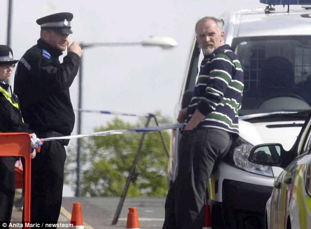 Paul Mosley, 45, pictured leaning on a van while an officer stands by the house where the fire took place, has been charged with the murder of six children