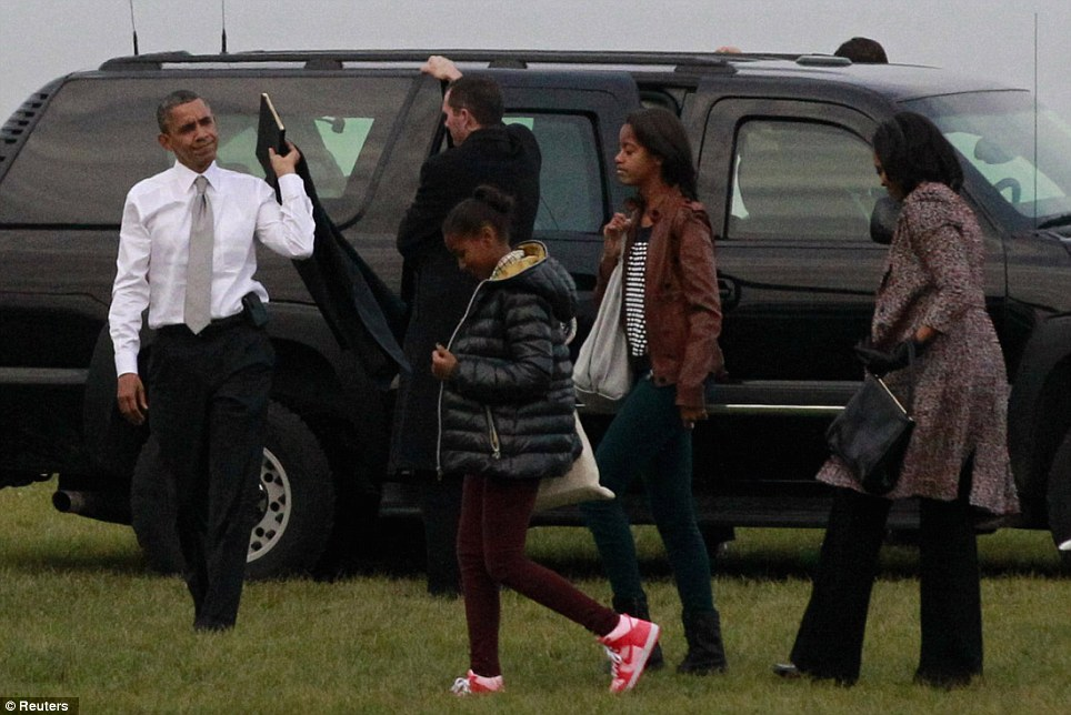 Let's go: Obama was joined by First Lady Michelle Obama and their daughters Malia (second from right) and Sasha as they left their Chicago hotel room