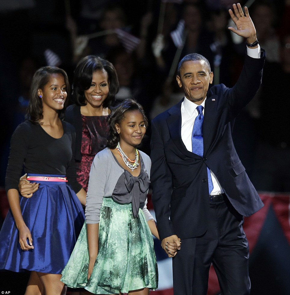 Proud: President Barack Obama waves as he walks on stage with his family in Chicago. Obama said his daughters are ¿two smart beautiful young women, just like their mother¿