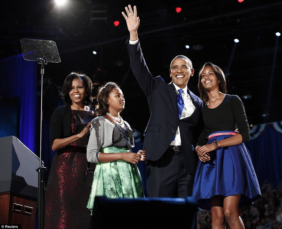 Beaming: Barack Obama puts his arm around Malia as he waves to supporters during his election night victory speech