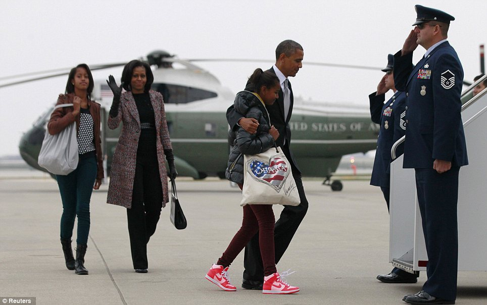 Jubilant: President Obama's daughter Sasha clutches an 'Obama' bag as the First Family boards Air Force One