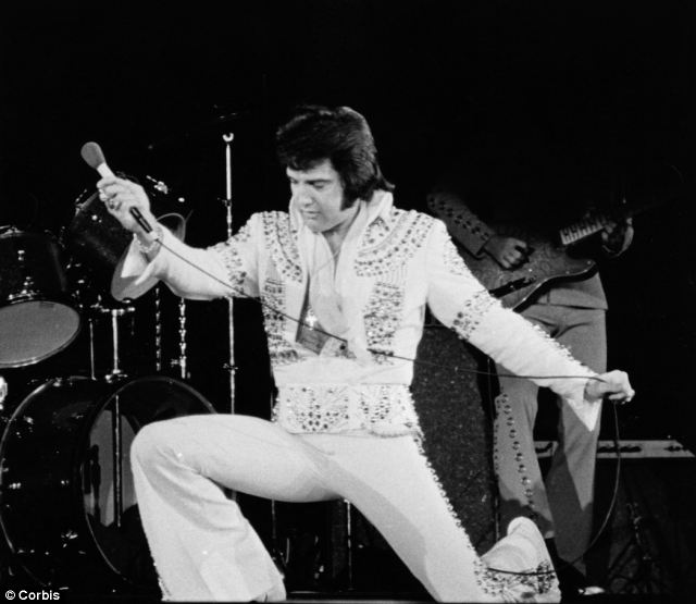Typical pose: Elvis performing his famous kneeling position during a performance in 1974