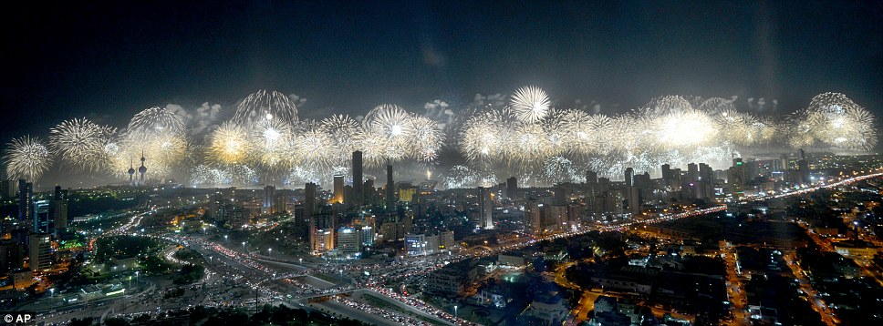 Bright white fireworks light up the high rise buildings in the capital of the oil-rich state