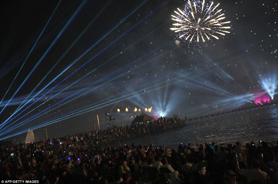 Thousands of people gather to watch fireworks and dramatic laser display which lights the sky near the Kuwait Towers
