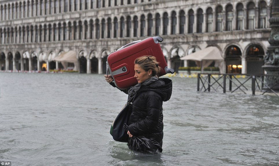 Tourists swim in Venices iconic St Marks Square as Floating City is flooded by high tides