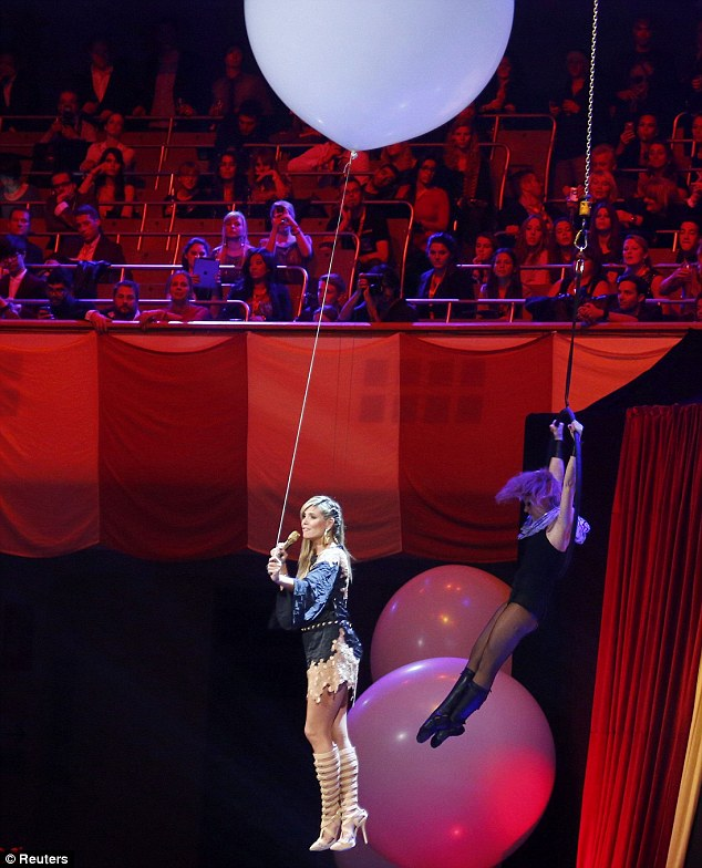 What an entrance: The host drops from the ceiling by a giant balloon wearing yet another outfit