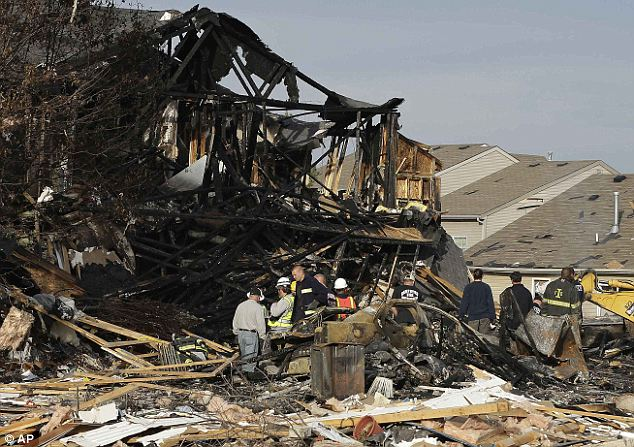 On scene: Emergency personnel work at the site of a home that was destroyed by the explosion that hit an Indianapolis neighborhood