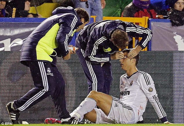 Treatment: Real Madrid's medical team attended to Ronaldo after he was caught by Navarro