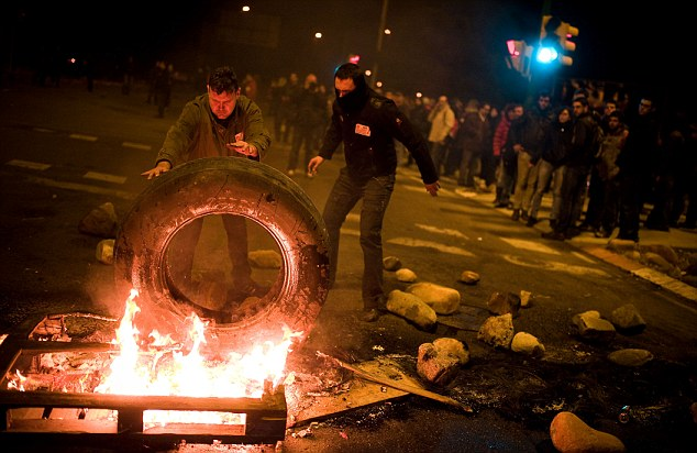 Demonstrators set up a barricade of burning tyres at the main entrance of Barcelona's biggest wholesale market part of a wave of anti-austerity protests happening across Europe